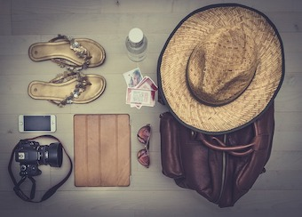 Beach accessories, including a hat, purse, camera, sunglasses and sandals